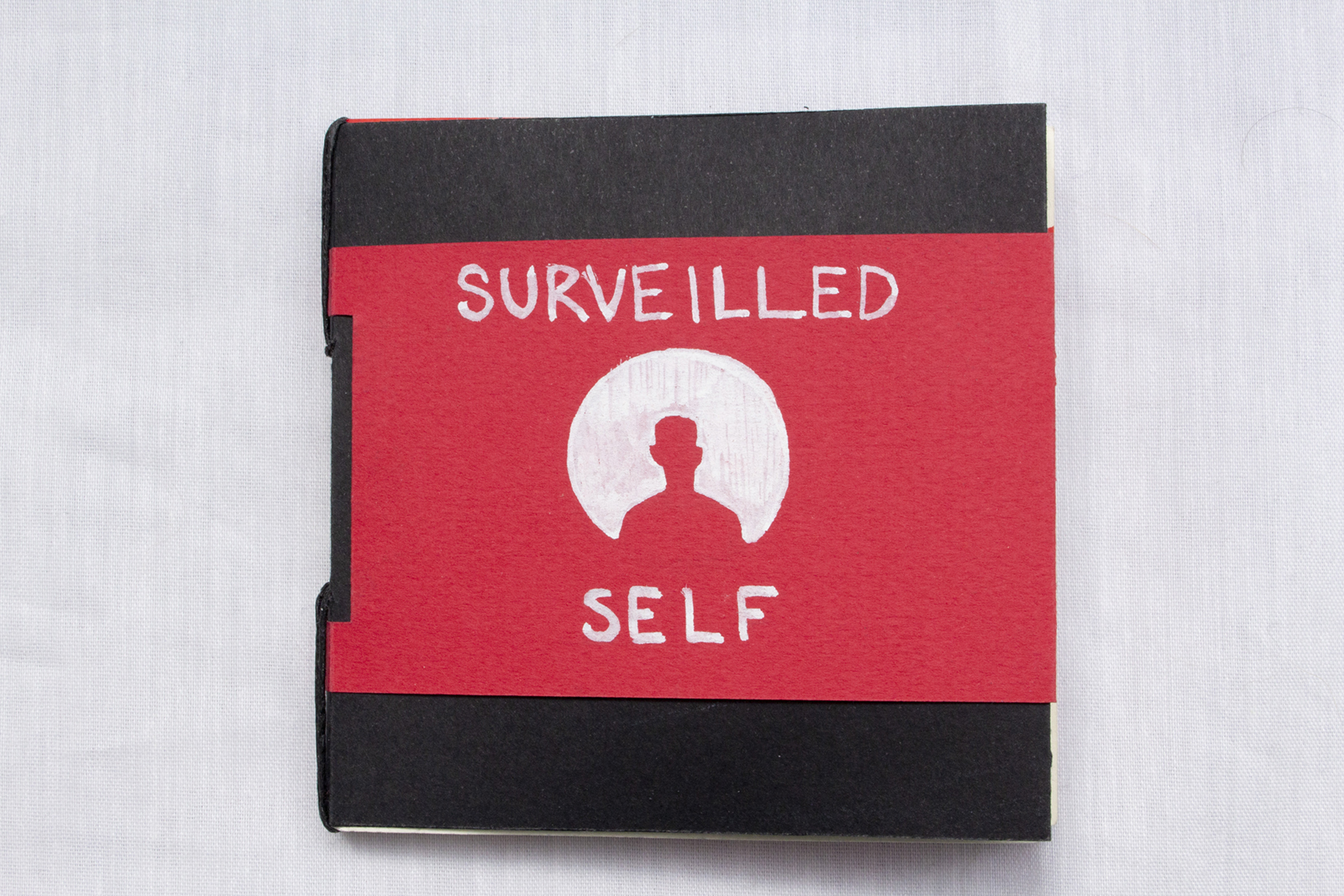 Front cover of Surveilled Self. Black paper cover with a red sleeve. A white circle with a person's silhouette is drawn.
