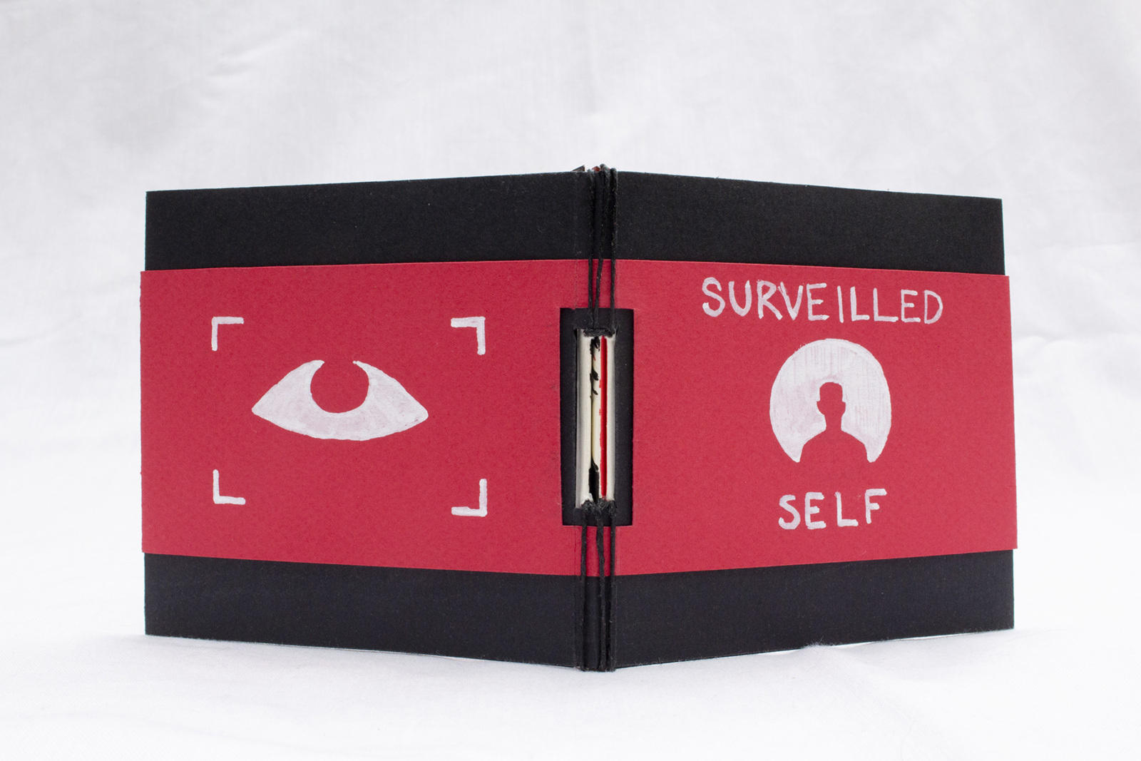 Entire cover of Surveilled Self. The buttonhole exposed spine binding is visible. Binding is black thread over paper cover.