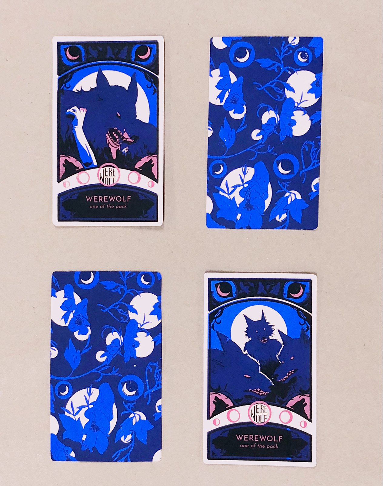 Screenprinted werewolf playing cards. Both cards are for the Werewolf role in the game. The front of the card is printed in four layers (mid-value blue, dark blue, black, and pink over pale orange paper, the back is just mid-value blue and midnight blue. The front shows the role, an illustration of a werewolf and wolfsbane framing elements. The back is a repeat pattern of eyes, moons and wolfsbane.